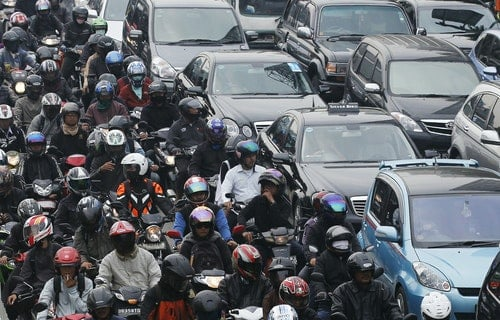 Motorists and vehicles are stuck in a morning rush hour traffic jam in Jakarta
