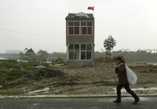 A woman walks past a nail house, the last house in this area, on the outskirts of Nanjing