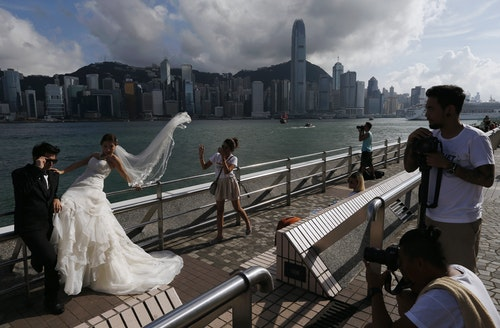 A couple takes wedding photos on the waterfront with a backdrop of Hong Kong's business Central district