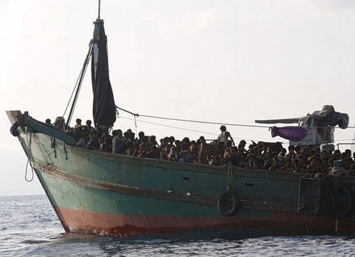 Migrants are seen aboard a boat tethered to a Thai navy vessel, in waters near Koh Lipe island