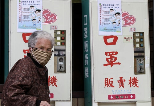 A woman wearing a medical mask walks past vending machines that sell masks outside National Taiwan University Hospital in Taipei