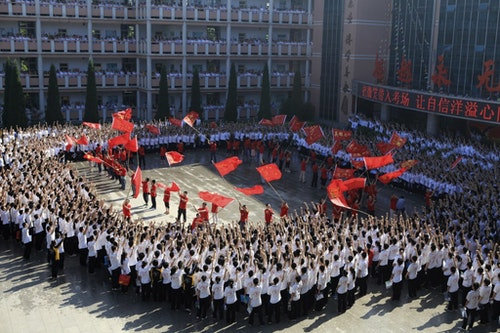 Students about to take the college entrance exam take an oath and teachers wave flags to boost morale. Photo Credit: Reuters