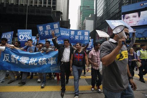 Protesters wave signs as they cross a street at Hong Kong's financial Central district