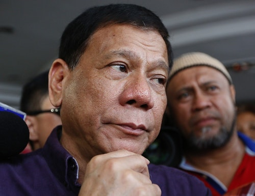 Mayor Rodrigo Duterte of Davao city in southern Philippines talks to supporters prior to addressing the crowd on his proclamation as the presidential candidate of the PDP-Laban political party Monday, Nov. 30, 2015 in Manila, Philippines. Duterte becomes the top five presidential bets in the next year's presidential elections. (AP Photo/Bullit Marquez)