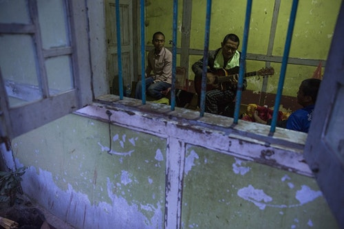 MYITKYINA, BURMA - JANUARY 26: Detainees play music while locked in a room at Pat Jasan headquarters on January 26, 2016 in Myitkyina, Burma. Pat Jasan is a Christian anti-drug group in Kachin State claiming over 100,000 members. Dissatisfied with the government's response towards widespread heroin use and poppy growing, the religious organization has taken matters into their own hands, organizing patrols, raiding houses, detaining drug dealers and users, and clearing poppy fields. Their brand of vigilante justice has been labeled extreme with some chapters accused of publicly beating those involved in the drug trade. (Photo by Taylor Weidman/Getty Images)
