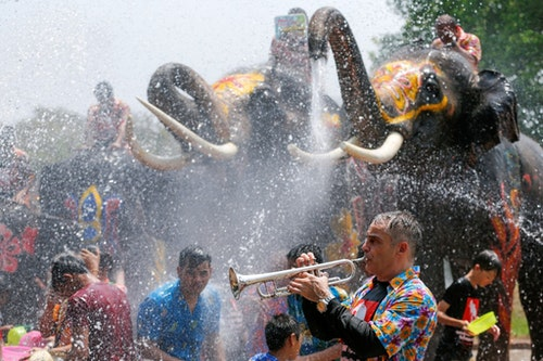 A man plays a trumpet while people are splashed by elephants with water during the celebration of the Songkran water festival in Thailand's Ayutthaya province, north of Bangkok, April 11, 2016. REUTERS/Jorge Silva TPX IMAGES OF THE DAY - RTX29E5Y