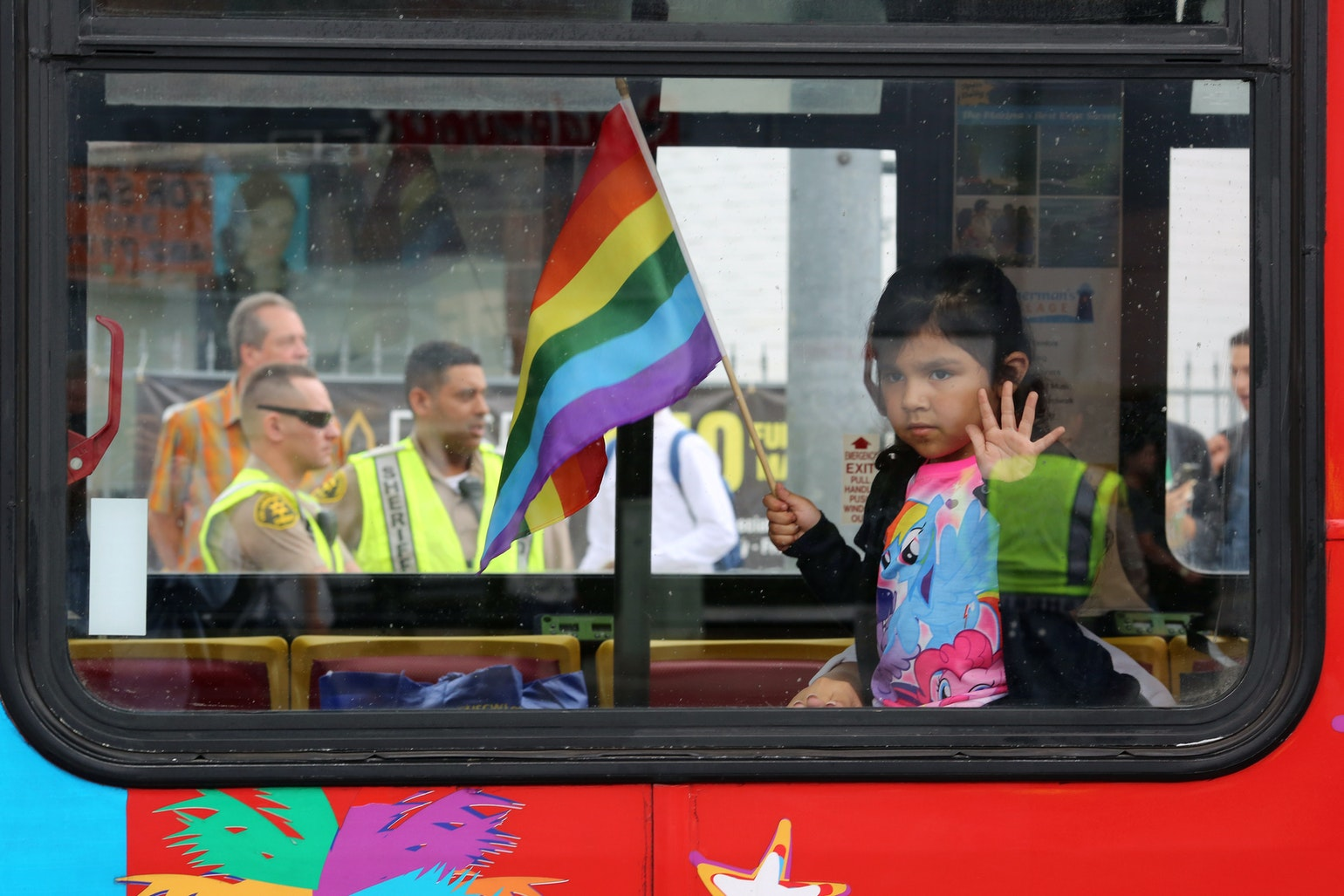 Los Angeles County Sheriff's deputies are seen behind a girl riding in a bus at the 46th annual Los Angeles Gay Pride Parade in West Hollywood