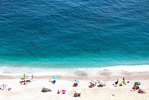 High altitude view of beautiful seashore with sunbathe people, vacation and holiday concept, ocean beach view with beautiful waves of clean transparent water and white sand